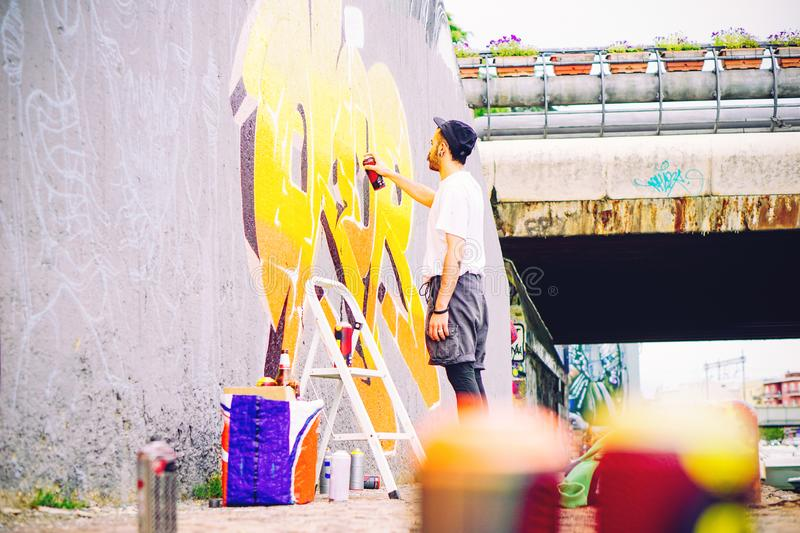 Street artist painting a colorful graffiti on a grey wall under bridge - Young graffiter writing and drawing murales royalty free stock photos