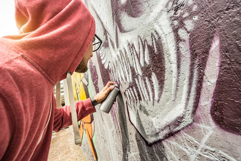 Street artist painting colorful graffiti on public wall - Modern. Art concept with urban guy performing and preparing live murales with multi color aerosol stock photo