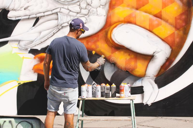 Street artist painting colorful graffiti on wall - Modern art concept with urban guy painting live murales with aerosol color spra. Copenhagen, Denmark - July 20 stock photos