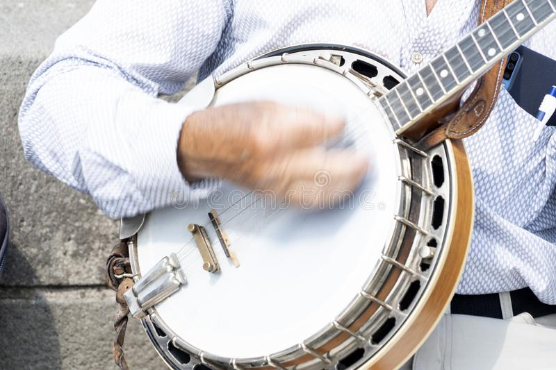 Street artist playing banjo musician detail of hands stock photos