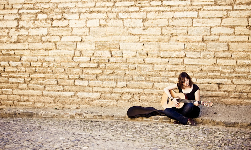 Street artist playing guitar. On the wall stock photo