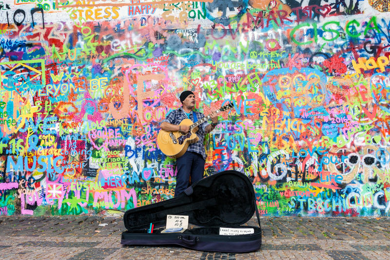 Street artist playing guitar. Prague, Czech Republic - June 27, 2016: Street artist playing guitar at the famous Lennon graffiti wall in old town of Prague royalty free stock images