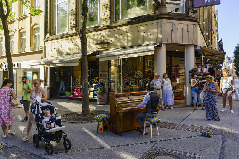 Street artist playing piano. Luxembourg, SEP 10: Street artist playing piano with passers on SEP 10, 2016 at Luxembourg stock photo