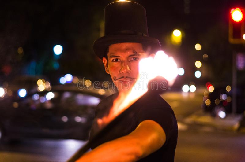 A street artist who makes a show in Lima - Peru, juggling a stick with fire at traffic lights stops. In front of stopped cars stock photo