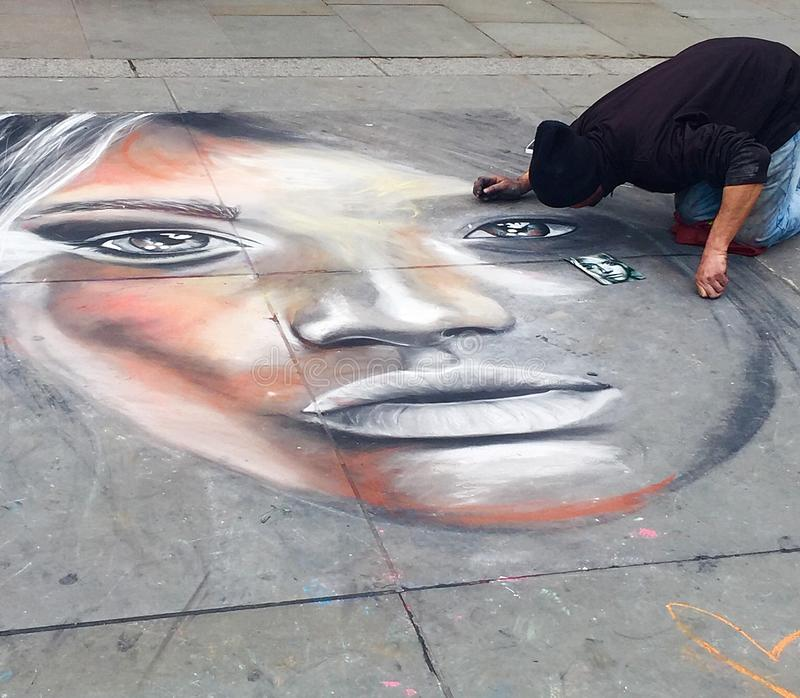 A street artist at work kneeling on the ground in London`s Trafalgar Square. A street artist kneels on the ground as he recreates the face of a beautiful woman stock photography