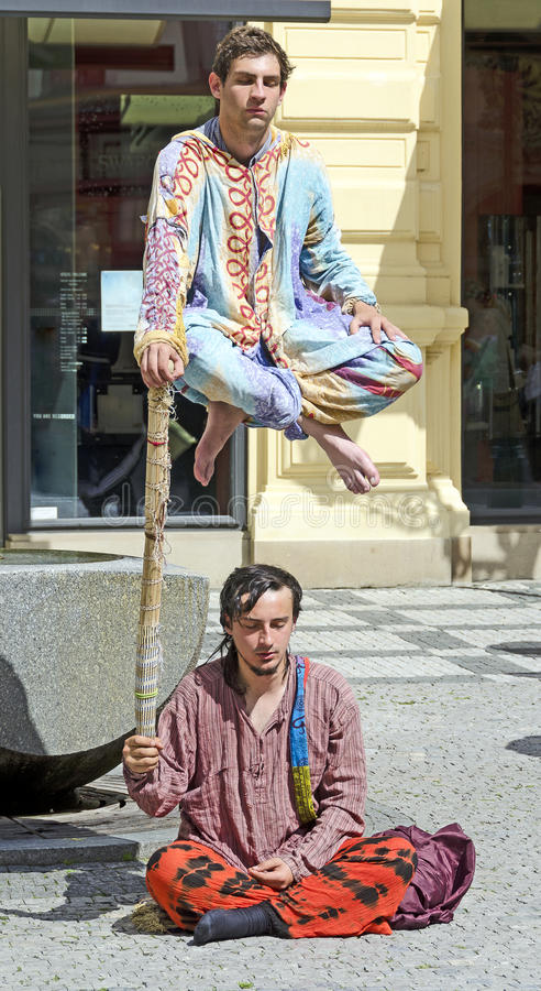 Street artists performing a hovering fakir. Two street artists performing a hovering fakir, Prague, Czech Republic stock photo