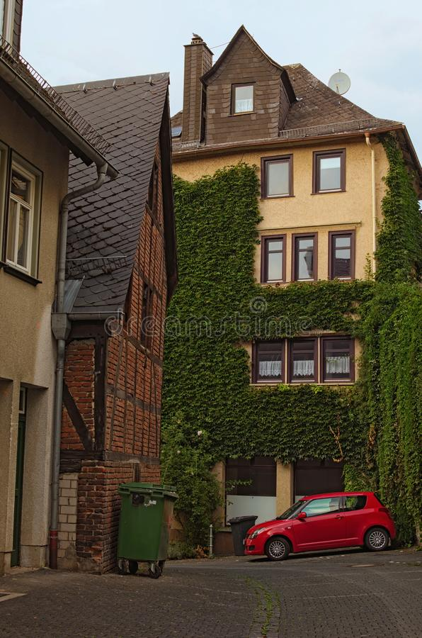 The street with a backyard of a big residential building. Small red car parked in the corner of backyard. Historic part of Wetzlar. City. State of Hesse stock photo