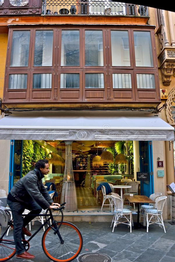 Street bar in a typical spanish building with white furniture and plant everywhere and a man biking royalty free stock image