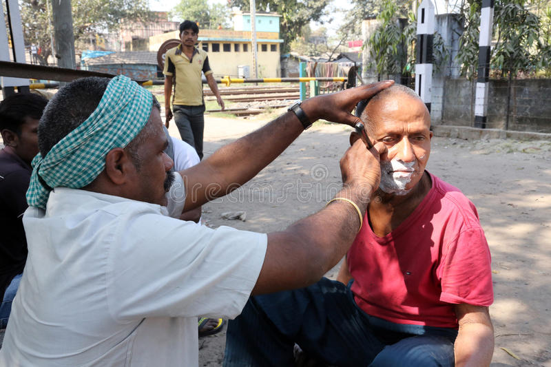 Street barber shaving a man on a street in Kolkata royalty free stock photo