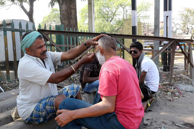 Street barber shaving a man using an open razor blade on a street in Kolkata royalty free stock images