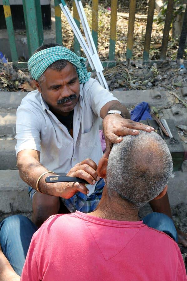 Street barber shaving a man using an open razor blade on a street in Kolkata stock image