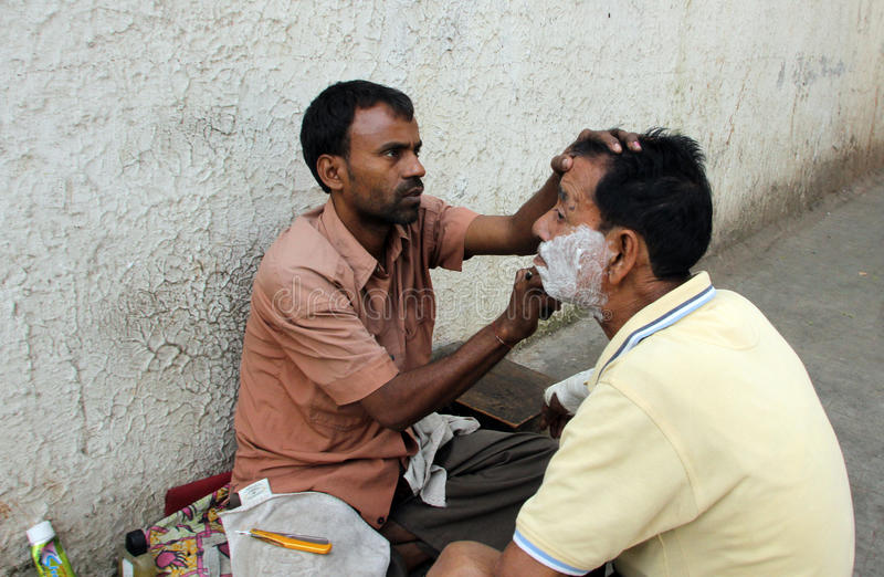 Street barber shaving a man using an open razor blade on a street in Kolkata stock photos