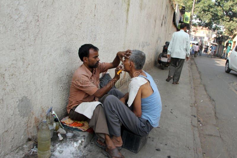 Street barber shaving a man using an open razor blade on a street in Kolkata stock photo