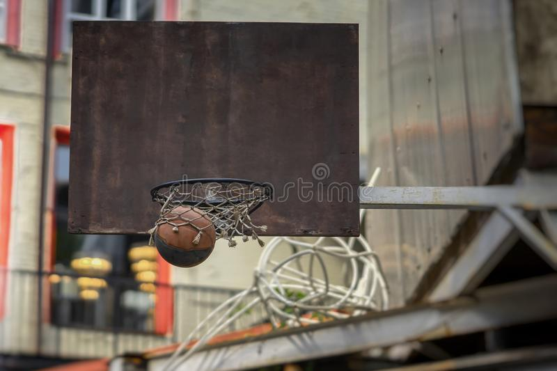 Street basketball game. Basketball shield, ball going through basket. Concept of sport, hit accuracy, active lifestyle. Accurate throw in basketball ring. Street stock photos