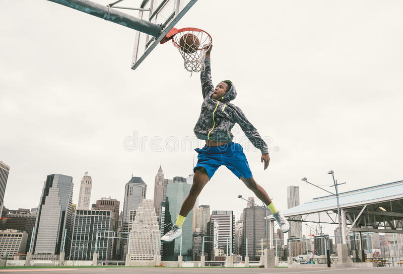 Street basketball player performing power slum dunk. Manhattan and New york city in the background stock photo