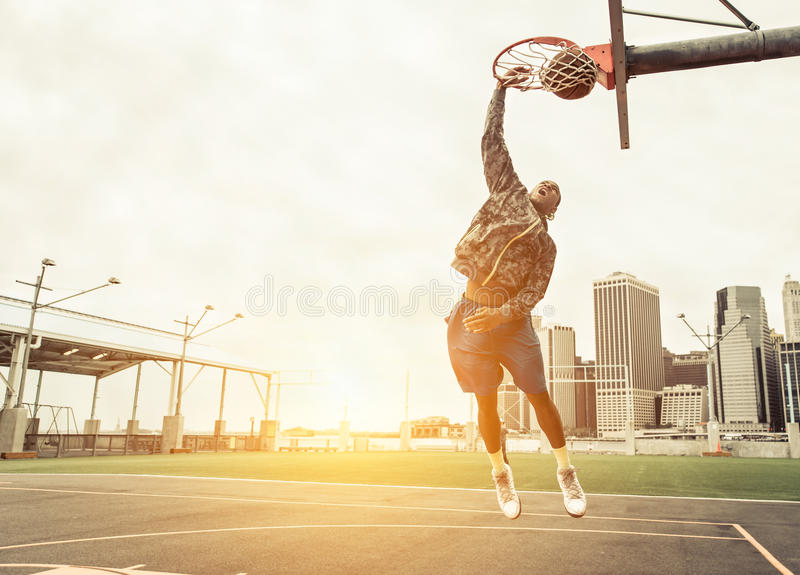 Street basketball player performing power slum dunk. Manhattan and New york city in the background stock image