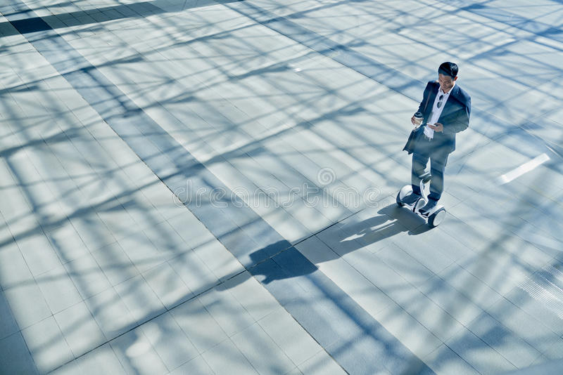 Street business. Young employee or manager on hoverboard standing on sidewalk stock image