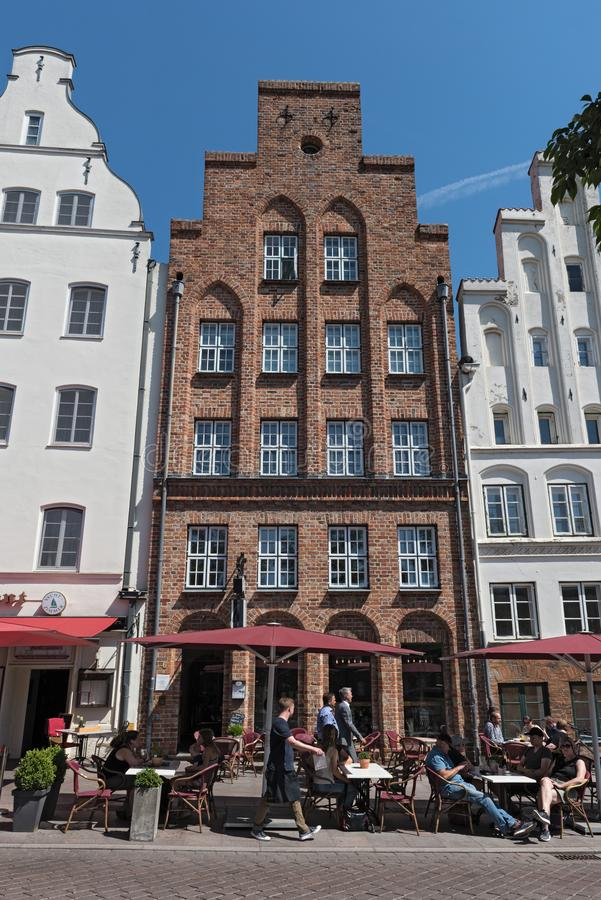 Street cafe in front of historic brick facade, lubeck, germany stock photos