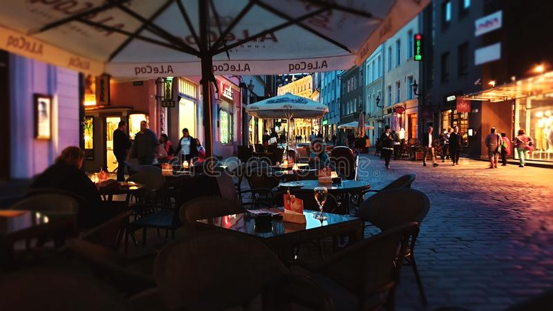 Street cafe at night old town of Tallinn ,Estonia, 20,08,2019 rainy night lamp reflection on glass wine girl sit on chair on table royalty free stock photos
