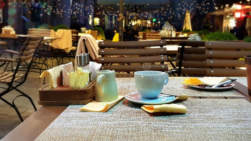 Street cafe at summer night  cup of coffee on table dinner relax holiday evening light decor design  modern reflection people walk. Summer night outside holiday stock images
