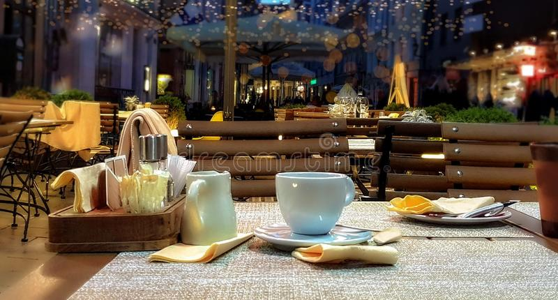 Street cafe at summer night  cup of coffee on table dinner relax holiday evening light decor design  modern reflection people walk. Summer night outside holiday stock image