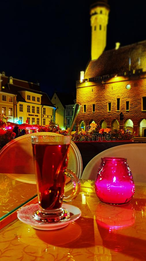 Street cafe table with glass of tea candle light flowers city lamp light red green colored town of Tallinn ,Estonia 20,. Street cafe table with glass of tea royalty free stock image