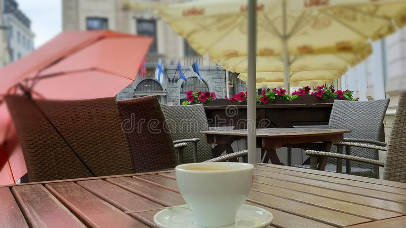 Street Cafe Table on top cup of coffee breakfast  and on chair pink umbrella. Travel to europa lifestyle old town of Tallinn ,morning breakfast stock photography