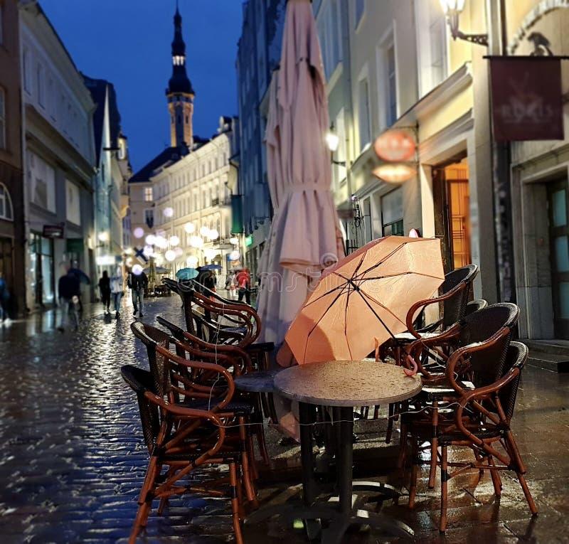 Night City Lights Rainy Season weather Tallinn Old Town Square Autumn evening in city street bokeh light  rainy night  umbrella. Street cafe tables ,Autumn royalty free stock image