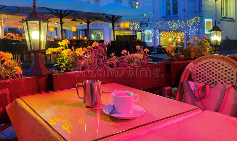 Summer holiday  light city  night Street cafe  bokeh blurring city light evening restaurant table cup of coffee on top view candl. Street cafe travel to Europe royalty free stock photography