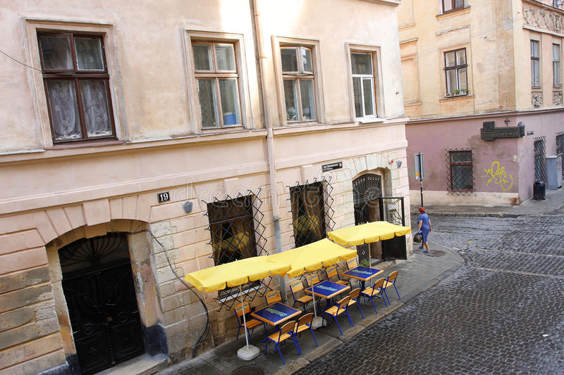 Street cafe and walking woman. On historical Armenian street in Lviv, Ukraine. Lviv's historic center has been on UNESCO World Heritage list sin.1998 royalty free stock images