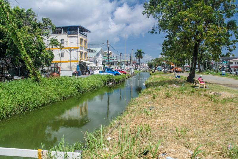 Street and a canal in Georgetown. GEORGETOWN, GUYANA - AUGUST 10, 2015: View of a street and a canal in Georgetown, capital of Guyana stock photography