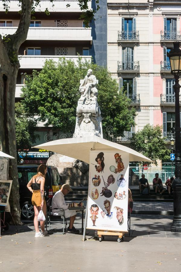 Street caricaturist painter working at La Rambla street. Las Ramblas is one of the most famous streets in the city. BARCELONA; SPAIN - june 16, 2019: Street stock image