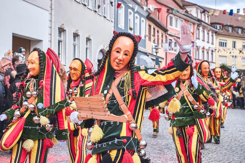 Beautiful and cheerful carnaval figure with bells. Street carnival in southern Germany - Black Forest stock image