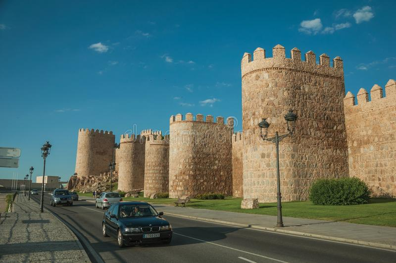 Street with cars beside stone towers in the walls around Avila royalty free stock image