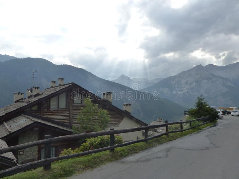 Street with a characteristic wood chalet next in Val di Suza in Italy. Travel destination. Summertime and holiday time. Sky with white clouds. Late afternoon royalty free stock photo