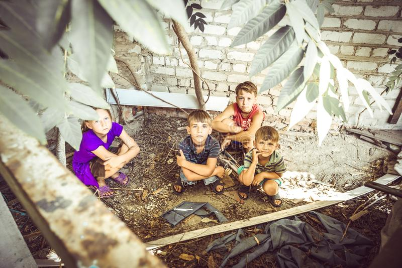 Street children sit in the trash in the corner of an abandoned house. Staged photo royalty free stock photo