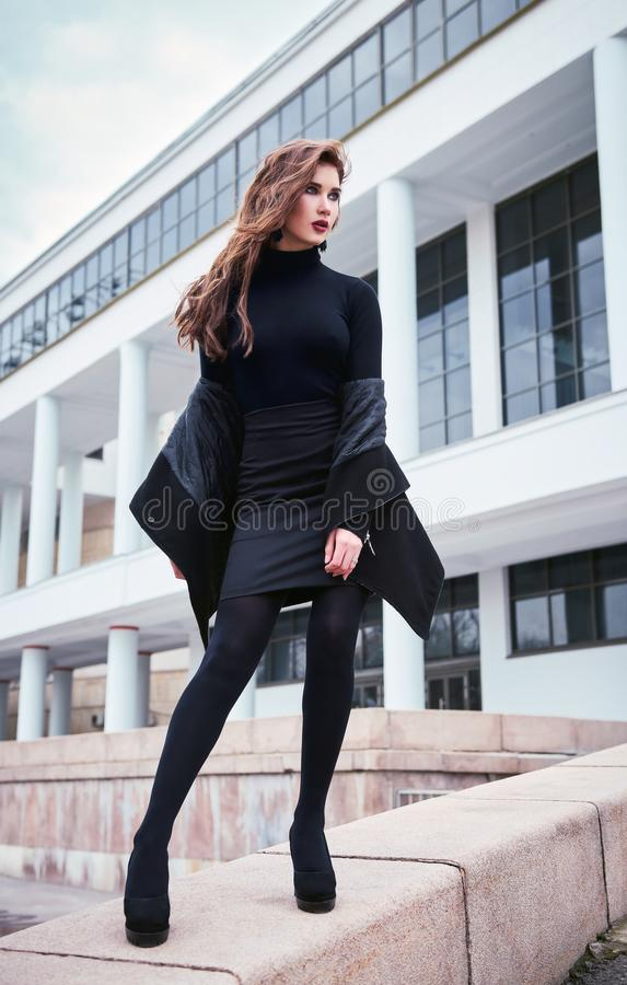 Street city fashion: portrait of beautiful young girl in black royalty free stock photos