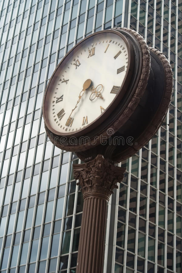 Street clock in front of a glass skyscraper royalty free stock images