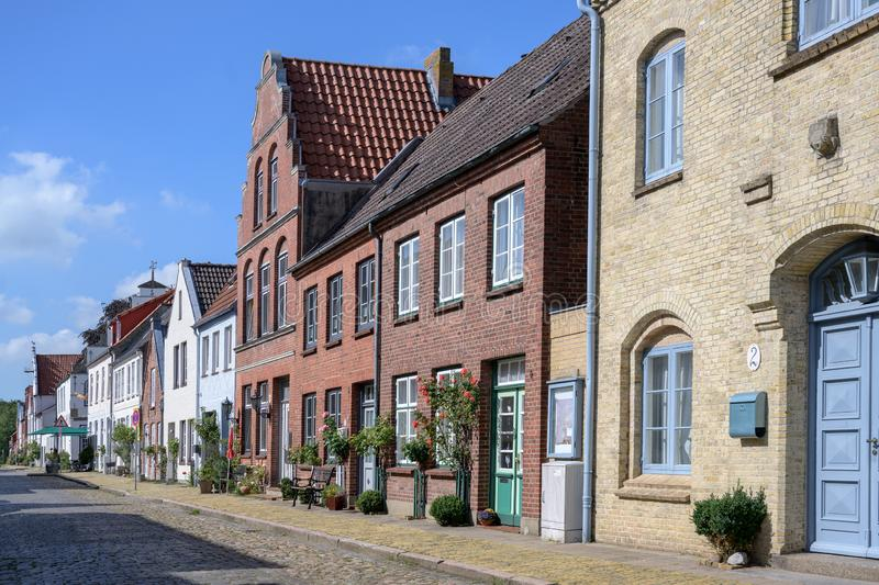 Street with cobblestone pavement and roses  in Friedrichstadt, the beautiful town and travel destination in northern Germany. Founded by Dutch settlers royalty free stock photo