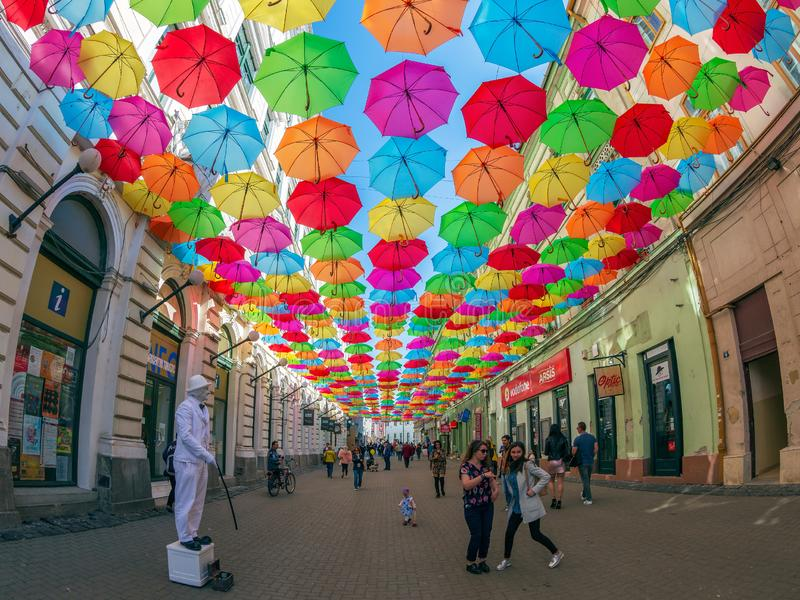 Street with colored umbrellas in Timisoara, Romania. TIMISOARA, ROMANIA - APRIL 20, 2019: Street with colored umbrellas, live statue and tourists royalty free stock photography