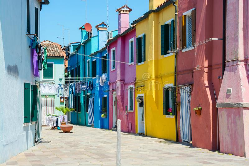 A street with colorful houses where laundry is dried on the island of Burano, Italy royalty free stock images