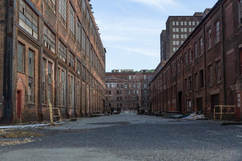 Street through a complex of derelict industrial buildings, daylight stock photos