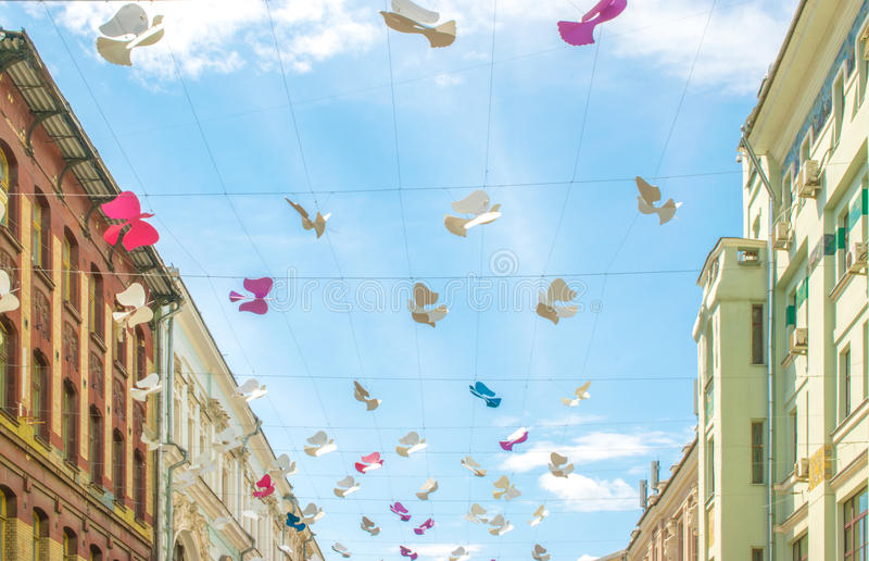 Street decorated with colored paper bird against sky royalty free stock photography