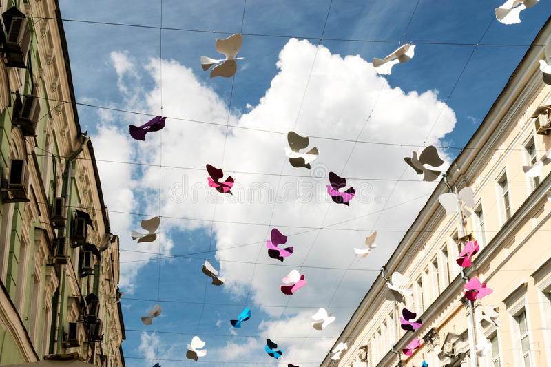 Street decorated with colored paper bird against sky royalty free stock image