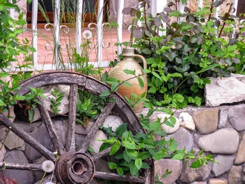 Street decoration of the cafe: flowers, an ancient cartwheel and old clay jug. stock images