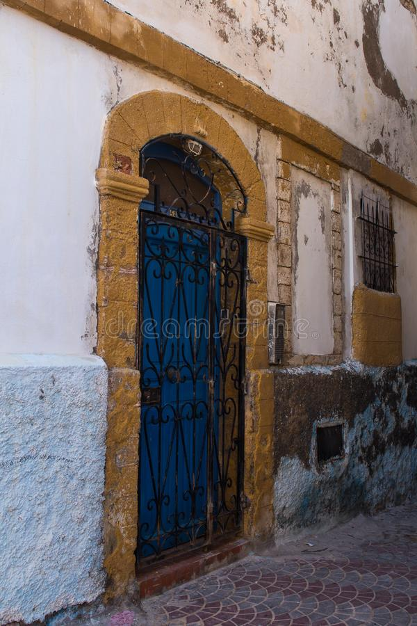 Old street in Safi, Morocco. Street with a detail of an old house. Bright blue door, iron ornate grating and a yellow frame. Safi, Morocco stock image