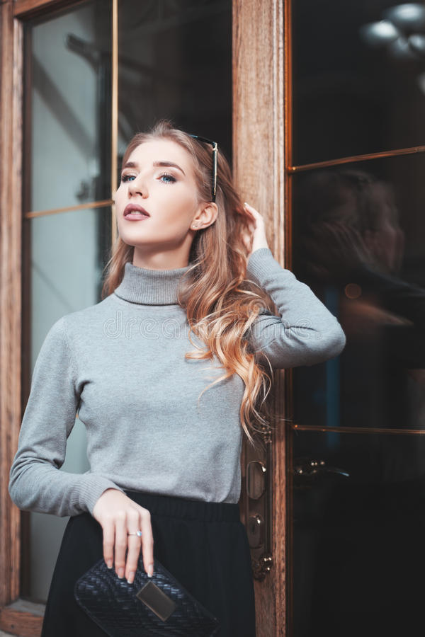 Street fashion concept: portrait of elegant young beautiful woman posing near the door. Waist up. City lifestyle royalty free stock image