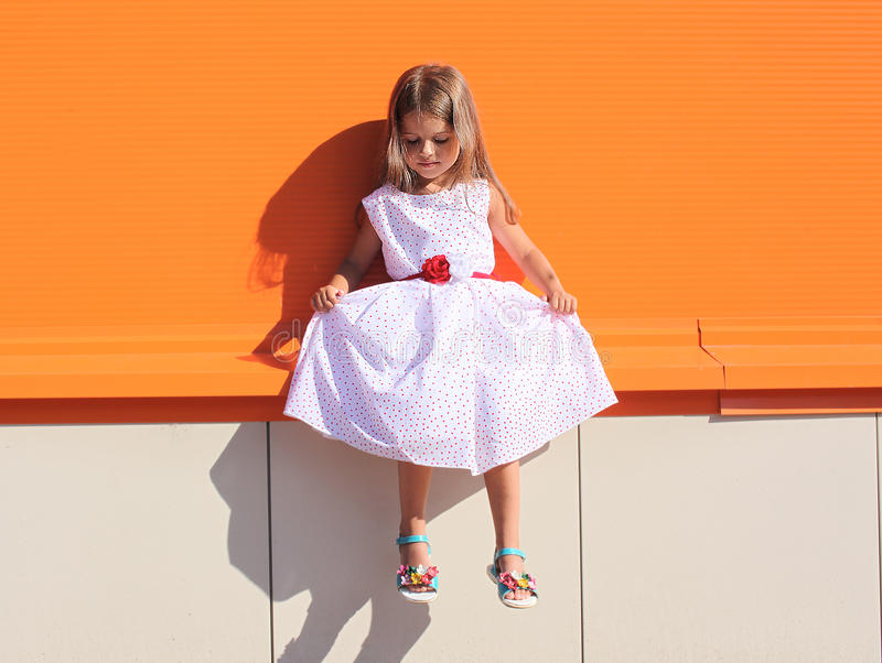 Street fashion kid, little girl in dress near colorful wall royalty free stock photo