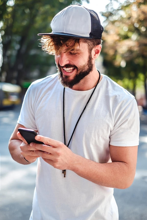Street fashion men looking at his phone. Street fashion man looking at his phone. Summer day royalty free stock photo