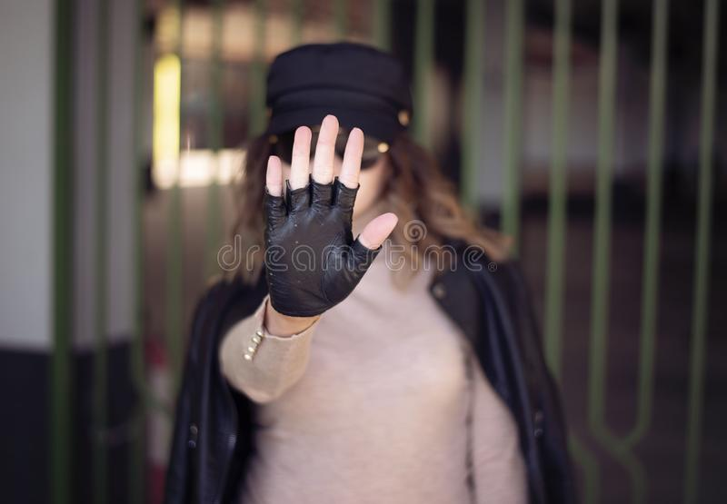 Street fashion outdoor photo of woman with dark hair in black leather jacket and sunglasses in defocus. Woman gesturing STOP with stock images